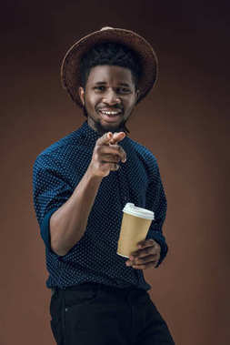 african american man with disposable coffee cup pointing on camera isolated on brown
