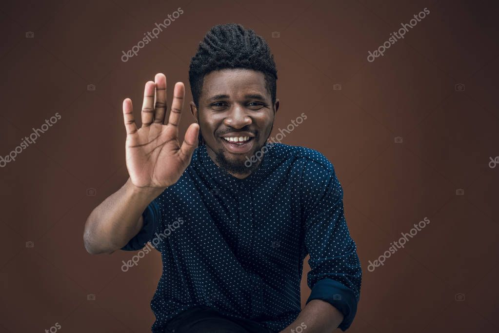 smiling african american man giving high five isolated on brown