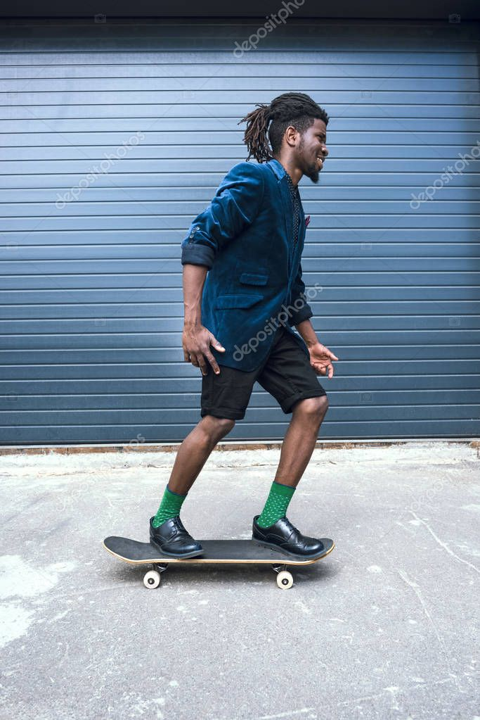 side view of stylish african american man in blue jacket skating on street