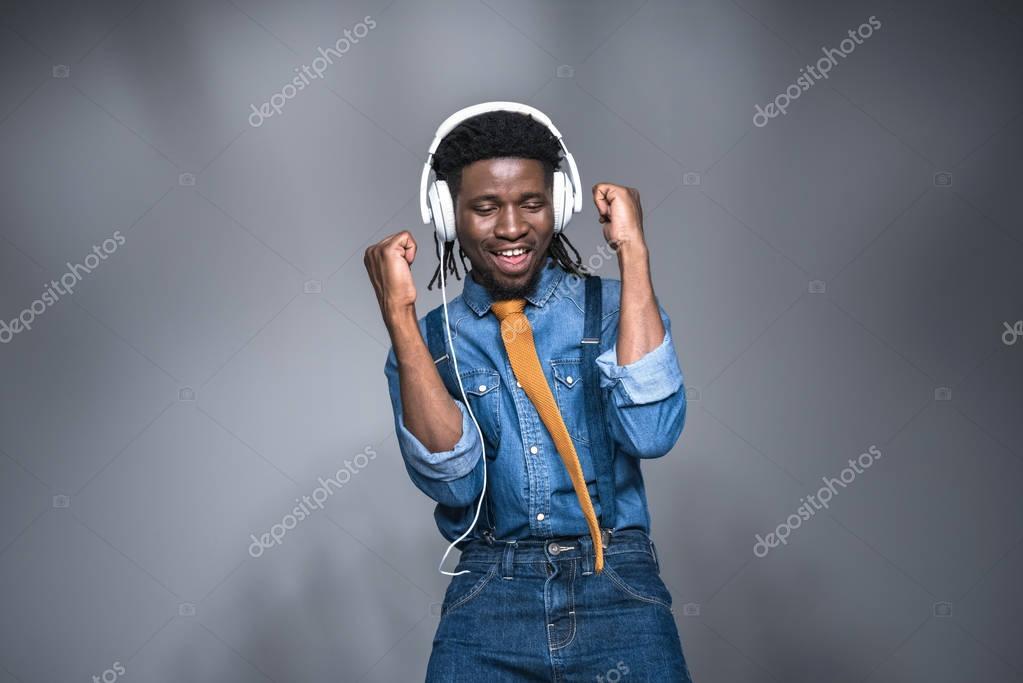 happy african american man listening music on gray