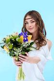 Fotografie šťastná mladá žena držící květinové kytice izolované na modré