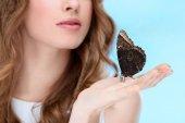oříznuté shot z krásné mladé ženy s motýlkem na skladě izolované na modré