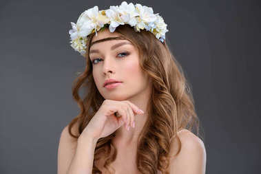 attractive young woman with curly hair in floral wreath isolated on grey