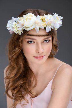 beautiful young woman with curly hair in floral wreath isolated on grey