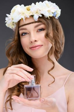 smiling woman with curly hair holding bottle of perfume isolated on grey