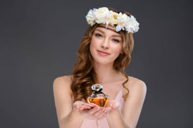 smiling young woman in floral wreath holding bottle of perfume isolated on grey