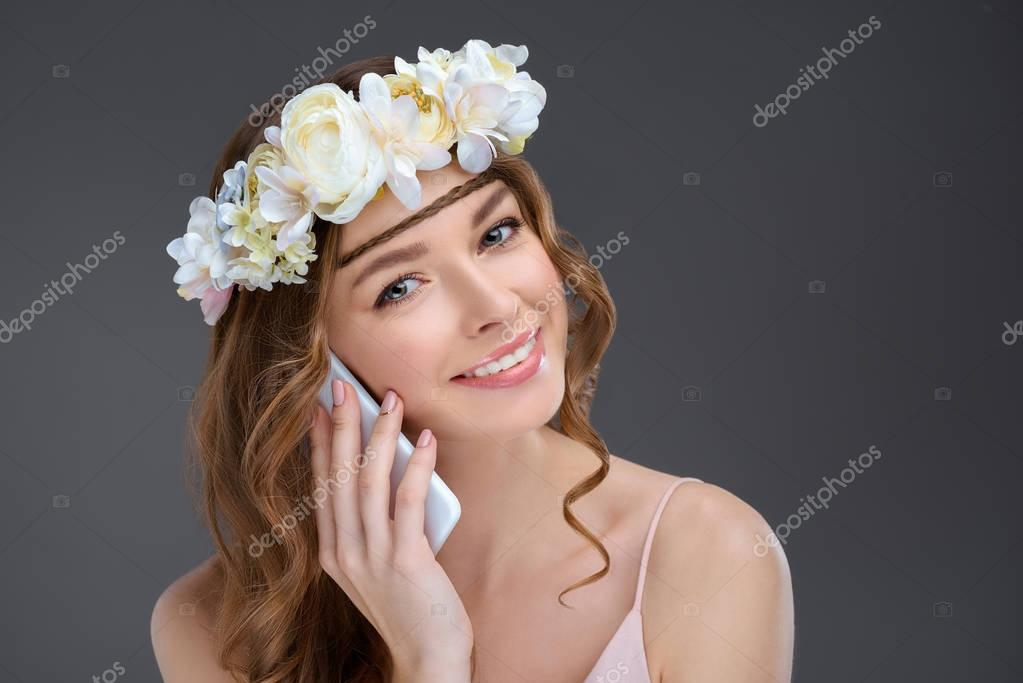 happy young woman in floral wreath talking by phone isolated on grey