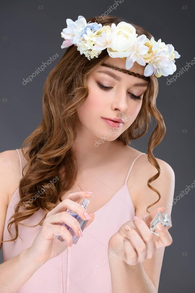 attractive young woman in floral wreath spraying perfume isolated on grey