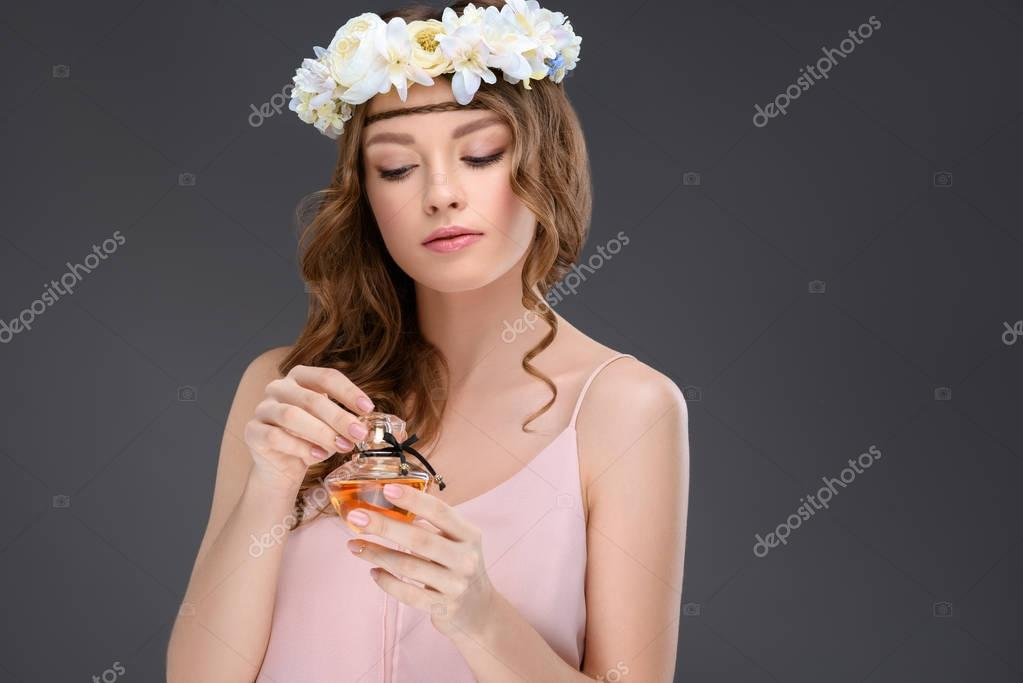 young woman in floral wreath holding bottle of perfume isolated on grey