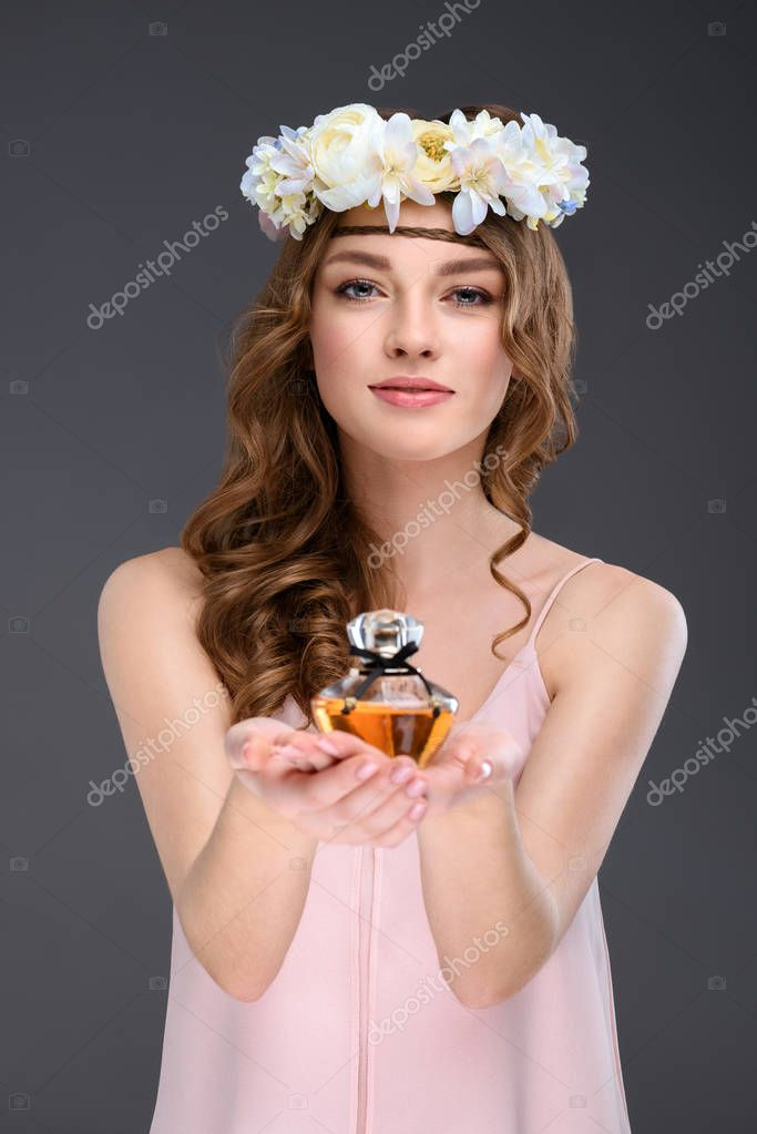 beautiful young woman in white floral wreath holding bottle of perfume isolated on grey