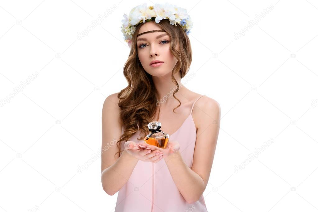 beautiful young woman in floral wreath holding bottle of perfume isolated on white