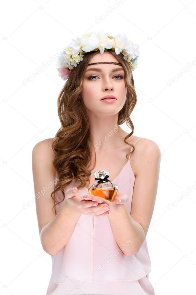 attractive young woman in floral wreath holding bottle of perfume isolated on white