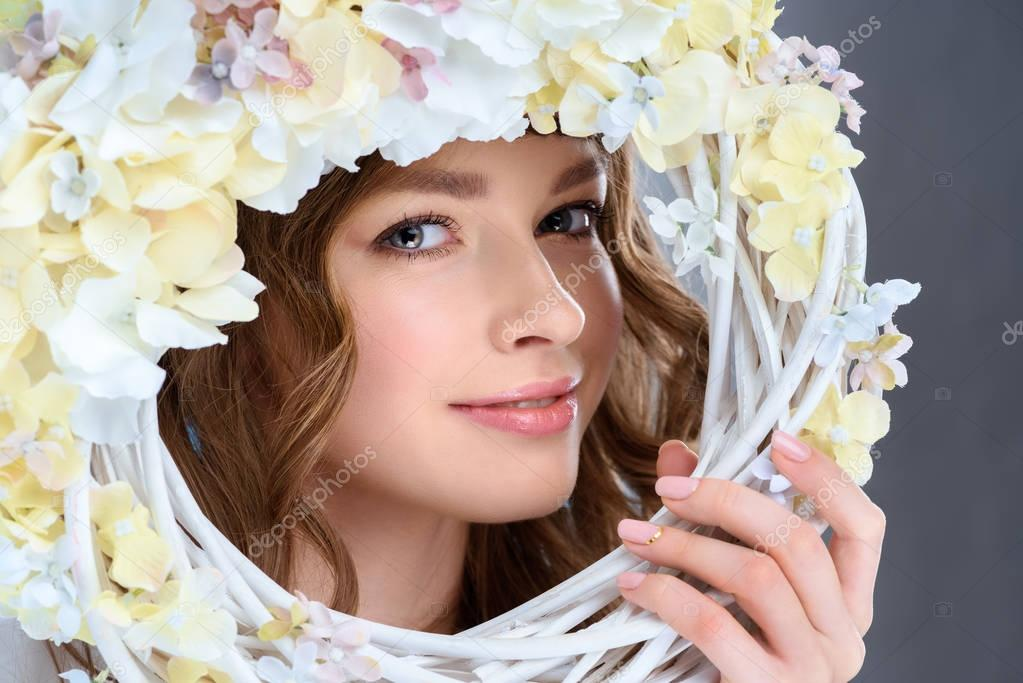 attractive young woman behind floral wreath