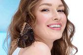 šťastná mladá žena s motýl na rameni