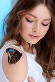 Smyslná mladá žena s motýl na rameni