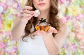 cropped shot of woman opening bottle of perfume on floral background