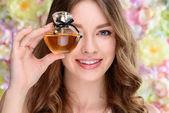 Detailní portrét s úsměvem mladá žena krycí jedno oko s parfém