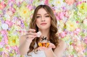 beautiful young woman opening bottle of perfume on floral background