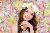 s úsměvem mladá žena v květinový věnec s kvetoucí růže bud