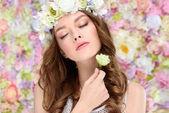 Smyslná mladá žena v květinový věnec s kvetoucí růže bud