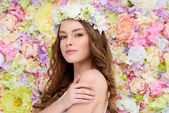 Fotografie sensual young woman in floral wreath on flral background