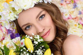 Fotografie close-up portrait of happy young woman with floral wreath and bouquet