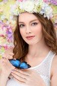 na straně s úsměvem mladá žena v květinový věnec s motýlkem
