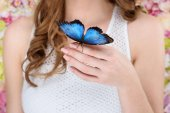cropped shot of woman with beautiful blue butterfly on hand