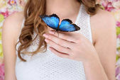 Fotografie cropped shot of woman with beautiful blue butterfly on hand
