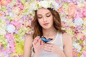 Smyslná mladá žena v květinový věnec s motýlkem na skladě