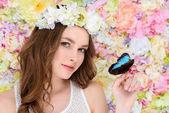 junge Frau im Blumenkranz mit Schmetterling an der Hand