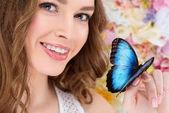 Detailní portrét s úsměvem mladá žena s motýlkem na straně