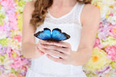 cropped shot of woman holding beautiful blue butterfly