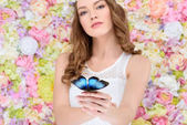 Photo attractive young woman in floral wreath with butterfly on hand