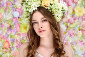 close-up portrait of attractive young woman in floral wreath