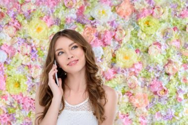 happy young woman talking by phone on floral background