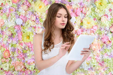 beautiful young woman using tablet on floral background