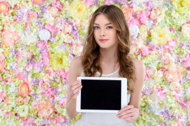 attractive young woman holding digital tablet on floral background