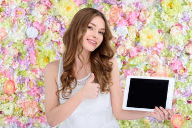 beautiful young woman with tablet showing thumb up on floral background
