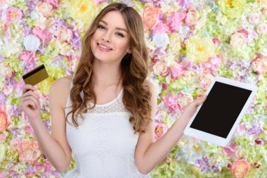 beautiful young woman with tablet and cretit card