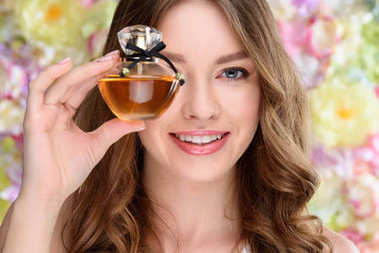 close-up portrait of smiling young woman covering one eye with bottle of perfume