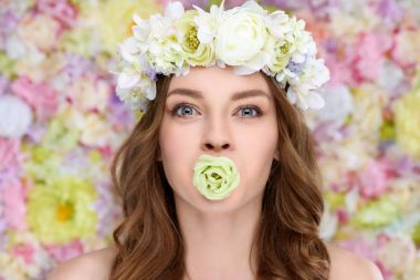 young woman in floral wreath with blossoming rose bud in mouth