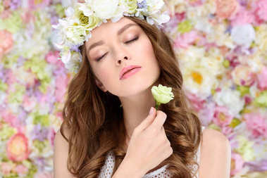 sensual young woman in floral wreath with blossoming rose bud