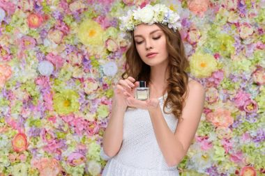 beautiful young woman in floral wreath with bottle of perfume