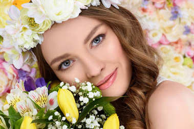 close-up portrait of happy young woman with floral wreath and bouquet