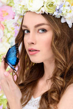close-up portrait of attractive young woman in floral wreath with butterfly on hand