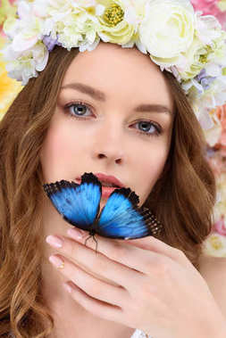 close-up portrait of sensual young woman in floral wreath with butterfly on hand