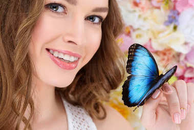 close-up portrait of smiling young woman with butterfly on hand