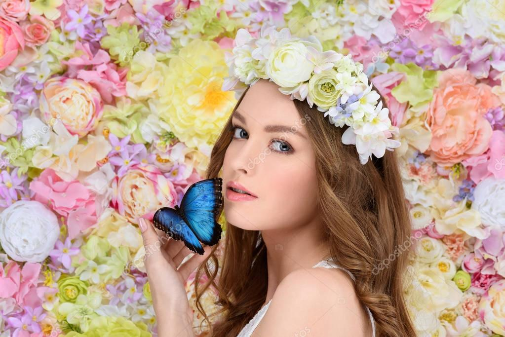 beautiful young woman in floral wreath with butterfly on hand