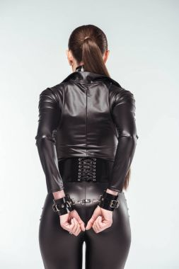 Rear view of hot girl in sexy leather costume and cuffs isolated on white